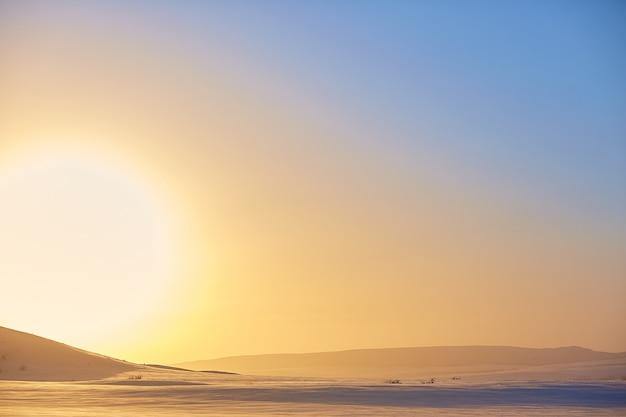 Pôr do sol de inverno em um fundo de montanhas nevadas