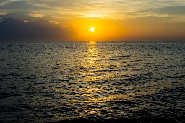 Pôr do sol de luz de ouro sobre a praia bangsean tailândia de marco do oceano