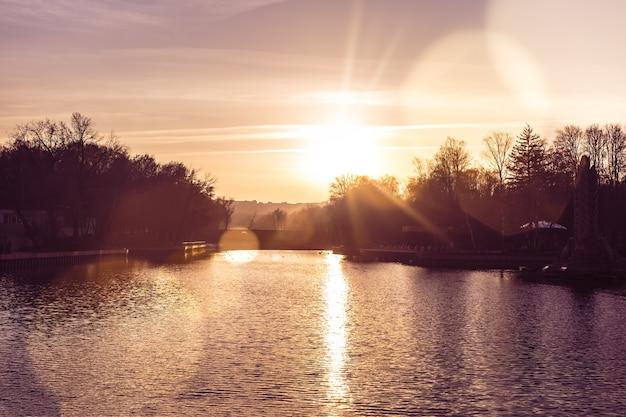 Pôr do sol de outono passado sobre o lago no parque da cidade o caminho do sol no reflexo da lente de água