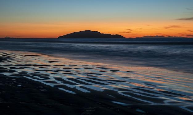 Pôr do sol de tirar o fôlego na praia otaki na costa kapiti, na ilha do norte da nova zelândia