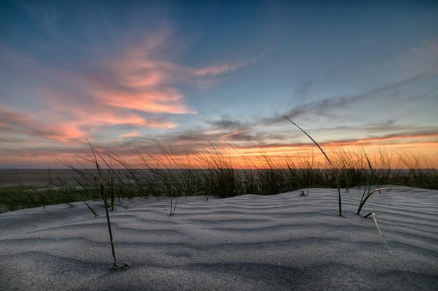 Pôr do sol de tirar o fôlego sobre a praia com uma costa arenosa