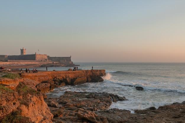 Pôr do sol de uma fortaleza marítima em portugal no oceano atlântico e famílias caminhando em um dia ensolarado