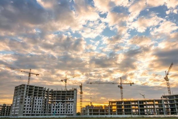 Pôr do sol de verão na construção de edifícios residenciais. muitos guindastes estão em operação