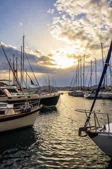 Pôr do sol de verão na costa do mar mediterrâneo em iates de luxo na marina e na vista da montanha