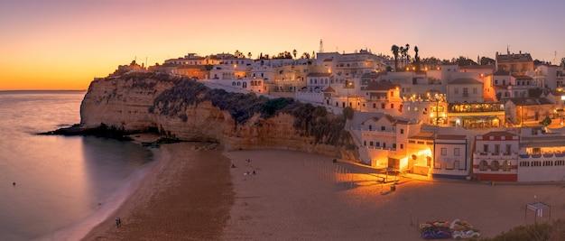 Pôr do sol de verão na praia de carvoeiro, na área do algarve, ao sul de portugal.