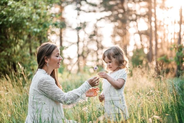 Pôr do sol de verão no parque ou floresta. filha do bebê em um passeio nas costas com a mãe. Foto Premium