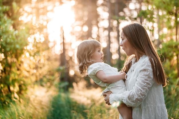 Pôr do sol de verão no parque ou floresta. filha do bebê em um passeio nas costas com a mãe.