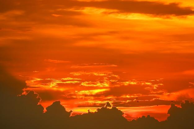 Pôr do sol de volta na última luz vermelha nuvem de silhueta de céu laranja