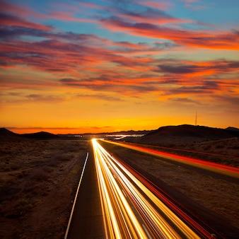 Pôr do sol do arizona na auto-estrada 40 com traços de luz de carros
