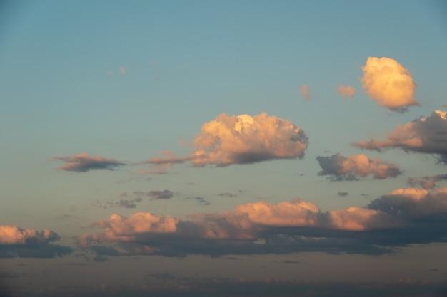Pôr do sol do céu azul de inverno com nuvens fofas rosa e amarelas separadas. o fundo celestial perfeito para suas fotos.