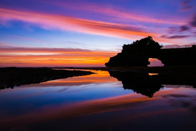 Por do sol do céu e reflexão bonitos no templo hindu pura tanah lot, bali, indonésia.