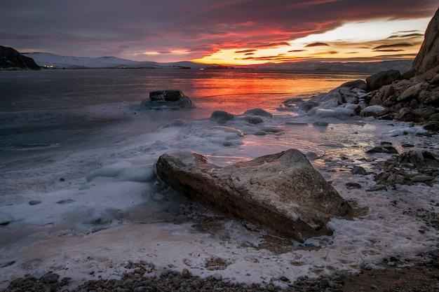 Pôr do sol do lago baikal, tudo está coberto de neve gelada