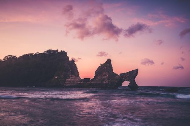 Pôr do sol do litoral da ilha de nusa penida da praia de atuh. floresta tropical na montanha e à beira-mar. foto panorâmica na rocha e ondas do mar. paisagem costeira em dias de bom tempo e céu nublado