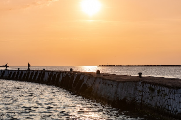 Pôr do sol do mar sobre o cais do báltico. sonhos de viagem e liberdade. bela vista do cais