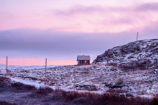 Pôr do sol do norte magenta com vista da casa na colina polar coberta de neve