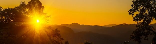 Pôr do sol dourado e silhueta de montanhas atrás.