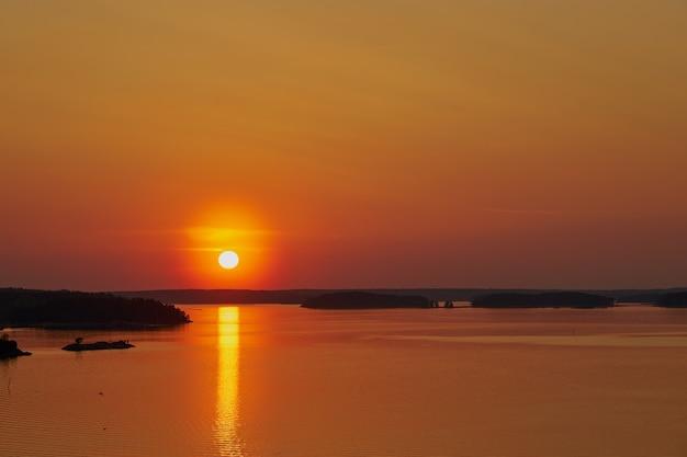 Pôr do sol dourado em naantali, finlândia. reflexo do sol na água. copie o espaço.