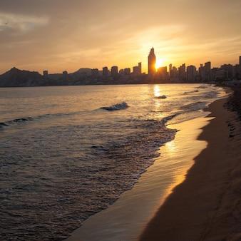 Pôr do sol dourado na praia poniente em benidorm, espanha