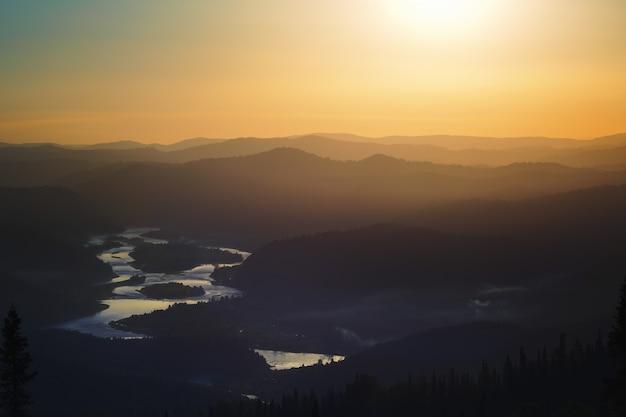 Pôr do sol dourado nas montanhas: silhuetas escuras das colinas, luz dourada na neblina, nuvens no céu azul, no fundo do vale reflexo na água do rio.