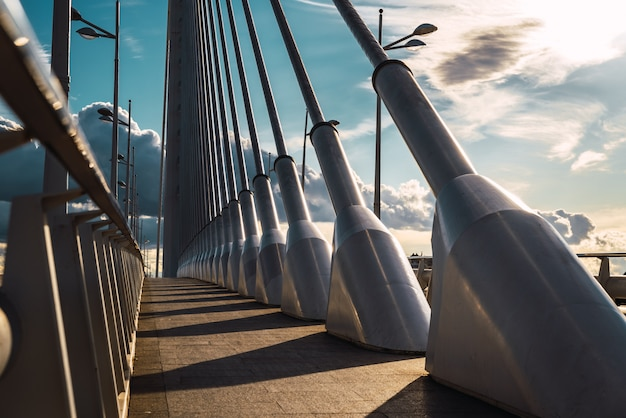 Pôr do sol dramaticamente sobre os cabos de aço de uma calçada em uma ponte urbana em valência