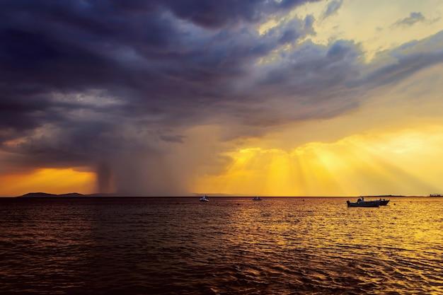 Pôr do sol dramático e tempestade chuvosa no mar
