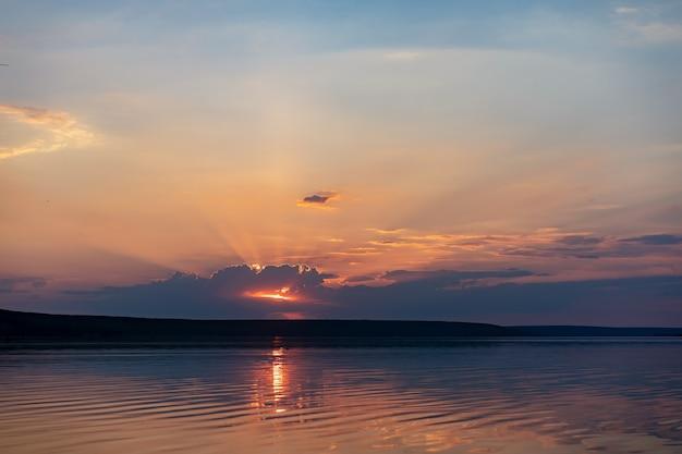 Pôr do sol dramático sobre a água do mar com céu nublado. fundo dourado colorido da natureza com águas calmas