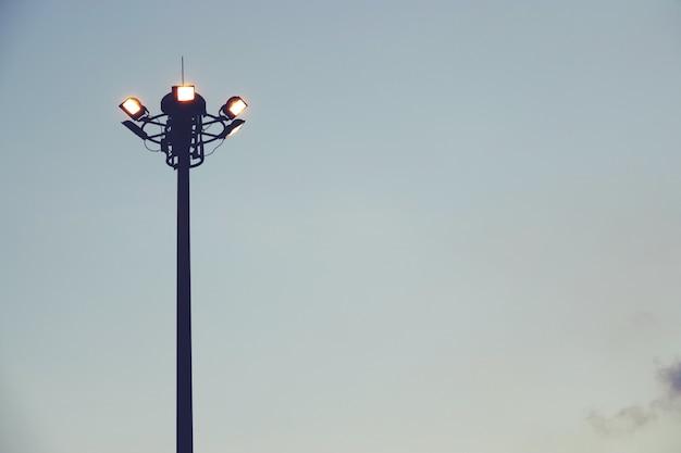 Pôr do sol e mastro alto com luzes de inundação no parque de esportes