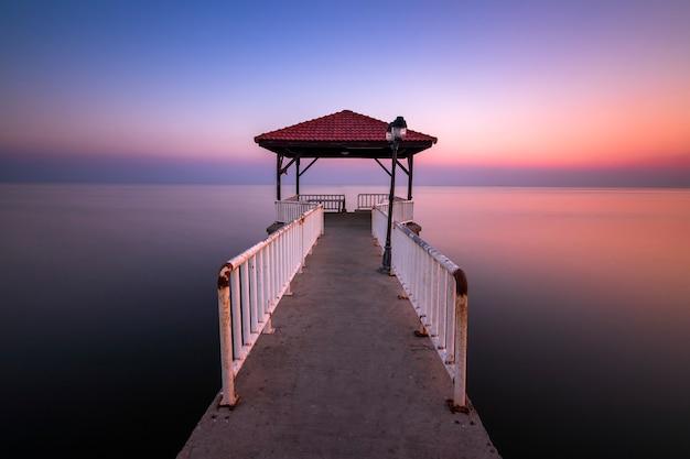 Pôr do sol e ponte sobre o mar na paisagem de chonburier