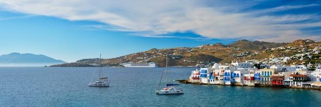 Pôr do sol em mykonos, grécia com navio de cruzeiro e iates no porto