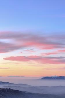 Pôr do sol em tom pastel sobre montanhas rochosas cobertas por nuvens