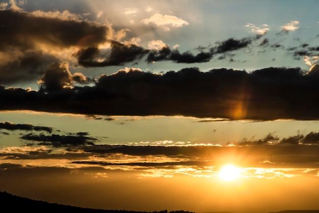 Pôr do sol em um dia com nuvens e raios de sol saindo deles na montanha.