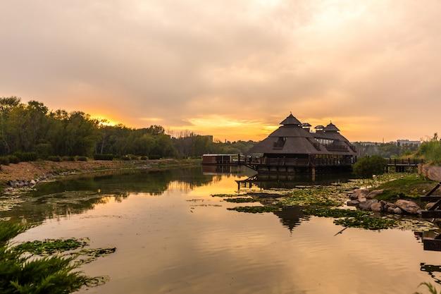 Pôr do sol em um lugar pitoresco. casa de madeira perto da qual um lago