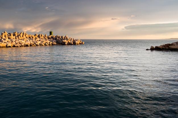 Pôr do sol em um quebra-mar de pedra na entrada de um porto