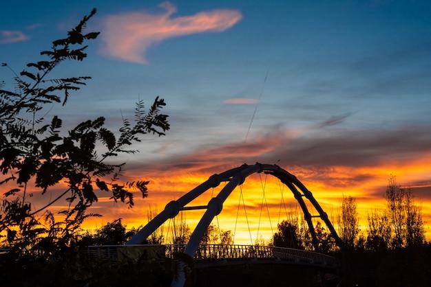 Pôr do sol em uma cidade do mediterrâneo com a silhueta da estrutura metálica de uma ponte suspensa