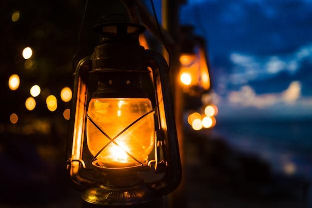 Pôr do sol em uma praia de ilha com lanternas iluminando a cena