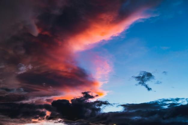 Por do sol escuro dramático da cor vermelha do alvorecer do crepúsculo do céu da nuvem.