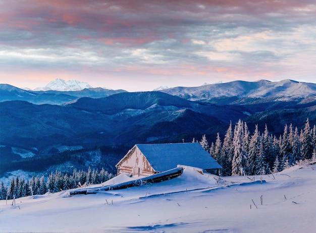 Pôr do sol fantástico sobre montanhas cobertas de neve e chalés de madeira