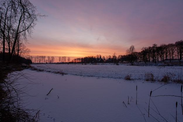 Pôr do sol hipnotizante perto do castelo histórico de doorwerth durante o inverno na holanda
