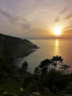 Pôr do sol hipnotizante refletido no oceano na cidade turística de san sebastian, espanha