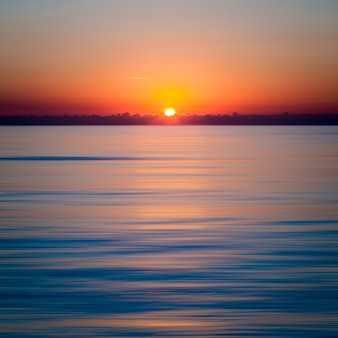 Pôr do sol hipnotizante sobre o oceano azul claro