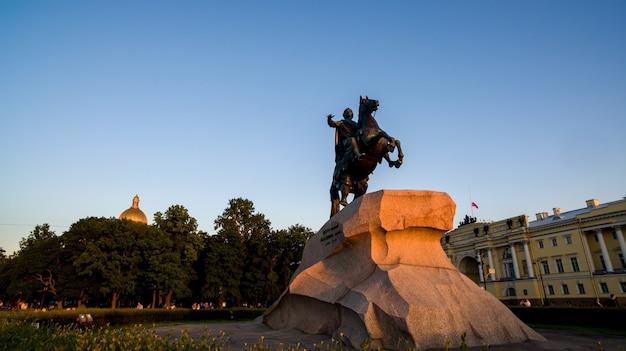Pôr do sol iluminado por monumento a cavaleiro de bronze