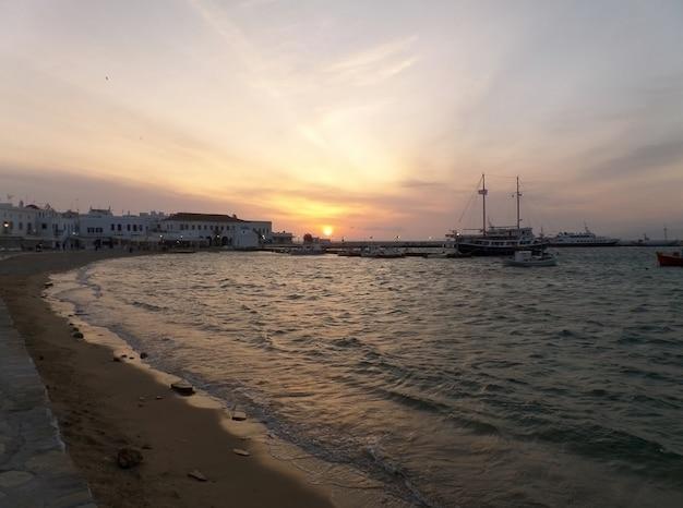 Por do sol impressionante na cidade de mykonos com muitos barcos no porto velho