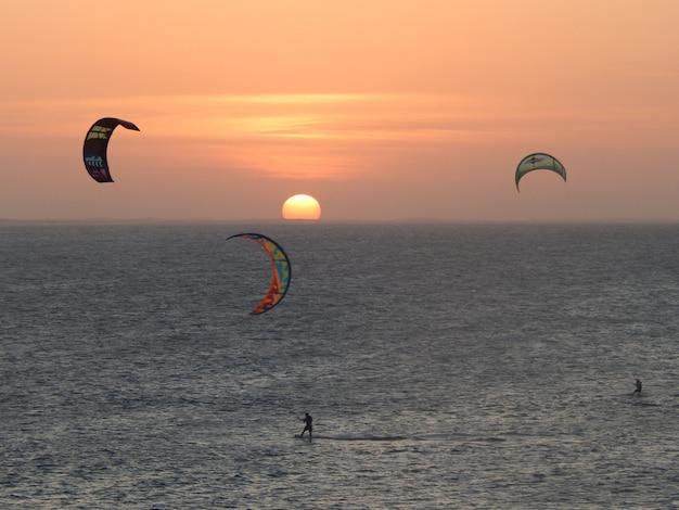 Pôr do sol incrível na praia com atletas kytesurfs praticando esportes