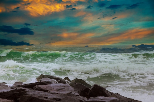 Pôr do sol incrível praia com horizonte infinito e figuras solitárias à distância e incríveis ondas de espuma.