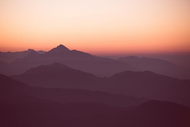 Pôr do sol incrível sobre as colinas e montanhas