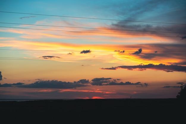 Pôr do sol incrivelmente lindo com um céu azul e amarelo lindo no pôr do sol no verão
