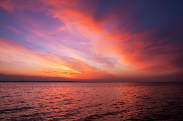 Pôr do sol laranja e vermelho mágico sobre o mar. nascer do sol sobre a praia
