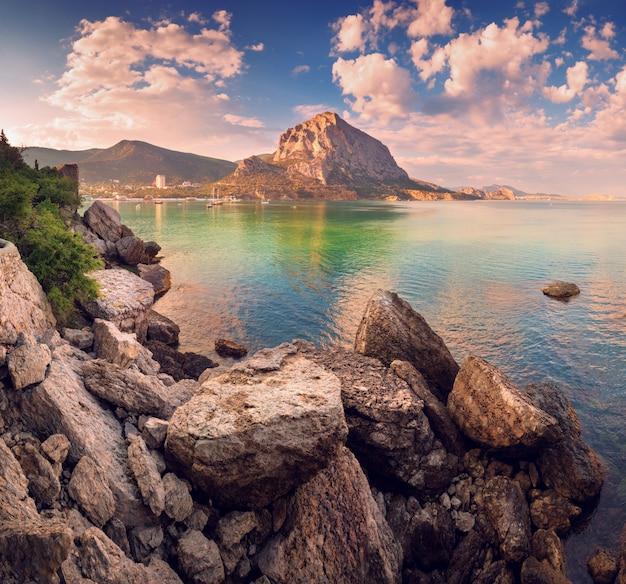 Pôr do sol lindo de verão no mar com montanhas e pedras