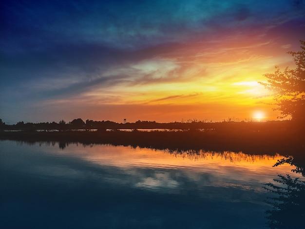 Pôr do sol lindo na natureza no céu de fundo de reflexão de noite