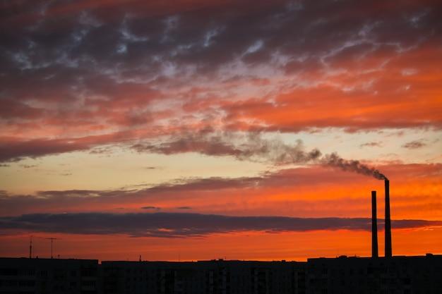 Pôr do sol mágico colorido. telhados de casas da cidade durante o nascer do sol. fumaça escura saindo da tubulação da usina termelétrica.